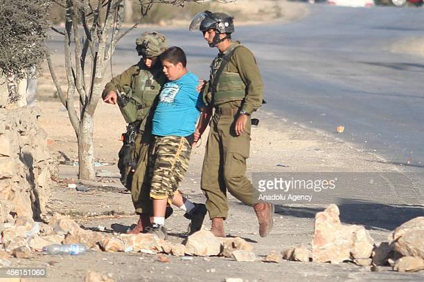 Israeli soldiers detain a Palestinian kid during a protest against the expropriation of Palestinian land by Israel and the Israeli Wall of Shame, the...