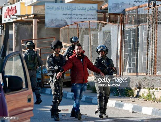 Israeli soldiers detain a Palestinian man during clashes between Palestinian demonstrators and Israeli troops in Ramallah near the Jewish settlement...