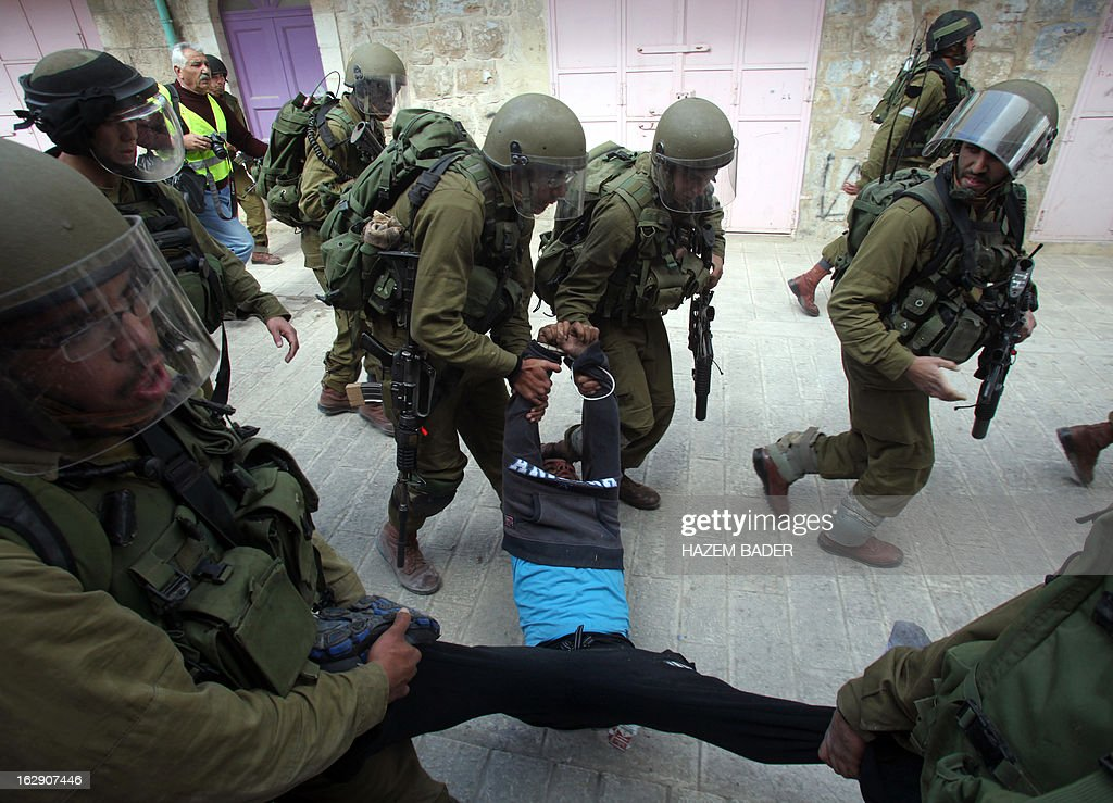 Israeli soldiers detain a Palestinian protester during clashes in the old city of Hebron on March 1, 2013 following a protest demanding the reopening of Shuhada Street, the one-time heart of the city. Flanked by a handful of Jewish settlement enclaves, the Shuhada Street was partially closed off in 1994 after local settler Baruch Goldstein opened fire on Muslim worshippers at the city's Al-Ibrahimi mosque, killing 29 of them.