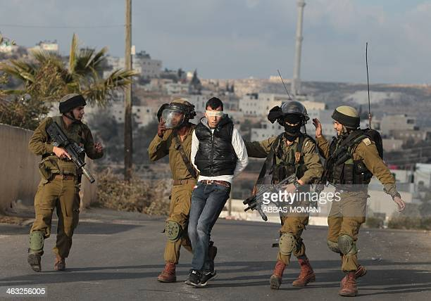 Israeli soldiers detain a Palestinian youth during clashes in the West Bank village of Silwad north of Ramallah on January 17 2014 following a...