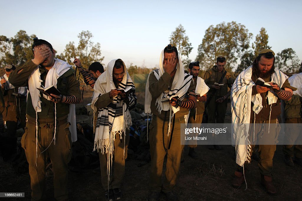 Israeli soldiers do their morning prayers in a deployment area on Israel's border with the Gaza Strip, on November 18, 2012 , in Israel. Israeli shelling of Gaza has entered its fifth day, with two media buildings being recently struck and several journalists injured. According to health officials in Gaza, at least 50 Palestinians have been killed since Israel launched operation Pillar of Defence. So far three Israelis have died in the exchange of missiles which followed an air strike on Wednesday that killed Hamas military chief Ahmed Jabari.