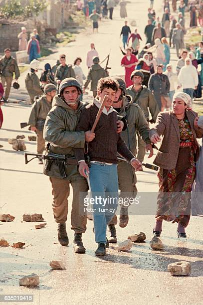Israeli soldiers escort an arrested man down a street littered with rocks thrown by Palestinian guerillas