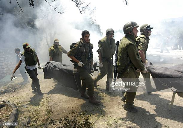 Israeli soldiers evacuate the bodies of dead troops from the still smoldering scene where a Hezbollah Katyusha rocket landed amongst army reservists...