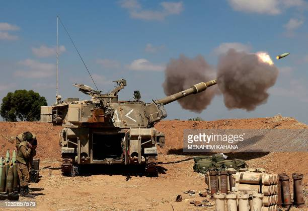 Israeli soldiers fire a 155mm self-propelled howitzer towards the Gaza Strip from their position near the southern Israeli city of Sderot on May 13,...