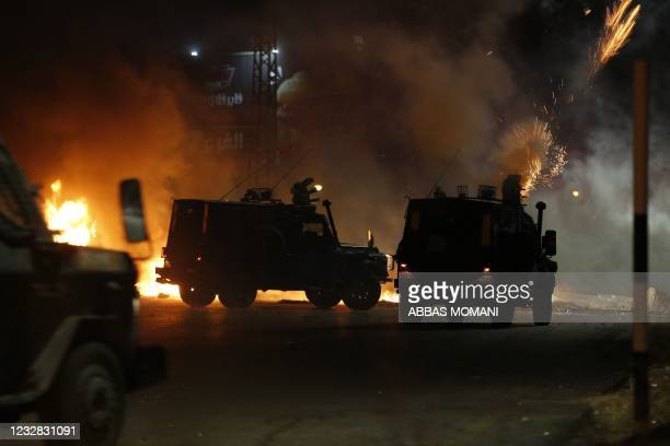 Israeli soldiers fire tear gas at Palestinian protesters during an anti-Israel protest over tension in Jerusalem, near the Jewish settlement of Beit...