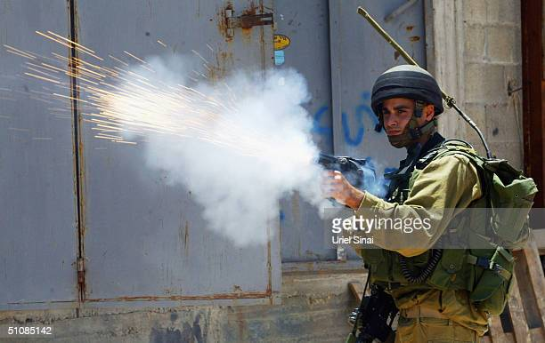 Israeli soldiers fire tear gas at Palestinian protestors as they demolish Palestinian buildings to make way for Israels separation barrier on July 20...