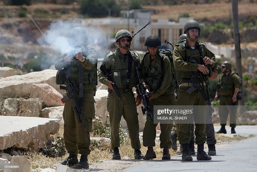 Israeli soldiers fire tear gas canister towards Palestinian and foreign peace activists during a demonstration against the construction of a section of Israel's controversial separation barrier in the West Bank village of Maasarah, near the biblical West Bank town of Bethlehem, on May 21, 2010. Israeli forces shot dead two Palestinian gunmen who had just infiltrated Israel from the Gaza Strip, media reported .