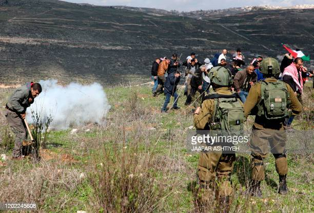 Israeli soldiers fire tear gas during a demonstration by Palestinian protesters in a field in Asira al-Qibliya town, south of Nablus, adjacent to the...
