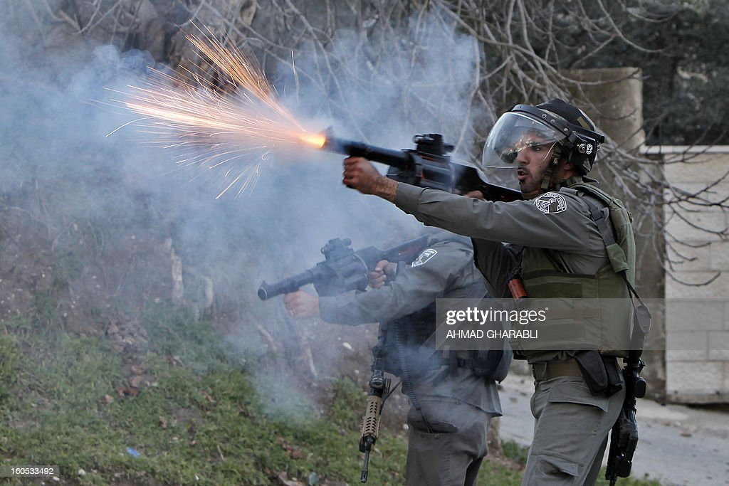 Israeli soldiers fire tear gas towards Palestinians as they remove them from a new camp set up to protest against Jewish settlements near the West Bank village of Burin on February 2, 2013.
