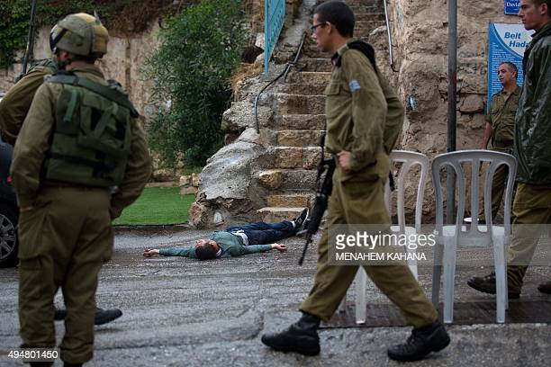 Israeli soldiers gather around the body of a Palestinian man who tried to stab a soldier at the Jewish settlement of Beit Hadassah in the center of...