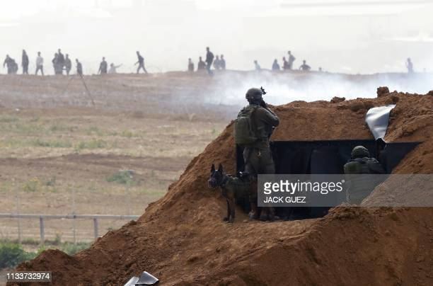 Israeli soldiers gather at a position over an earth barrier along the border with the Gaza Strip in the southern Israeli kibbutz of Nahal Oz across...