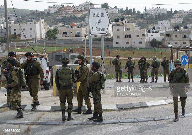 Israeli soldiers gather at the site of a stabbing attack at AlFawwar junction near the flashpoint city of Hebron on November 25 2015 A Palestinian...