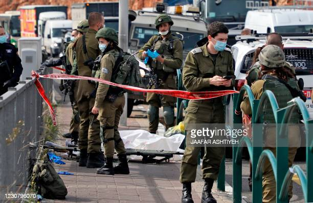 Israeli soldiers gather by the body of a Palestinian man who was shot dead reportedly while attempting a knife attack at the Gitai Avisar Junction,...