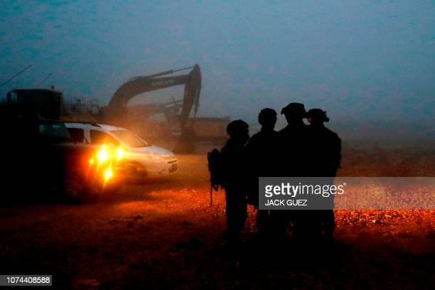 TOPSHOT Israeli soldiers gather near excavation equipment at work on border with Lebanon near the northern Israeli town of Metula on December 19 2018...