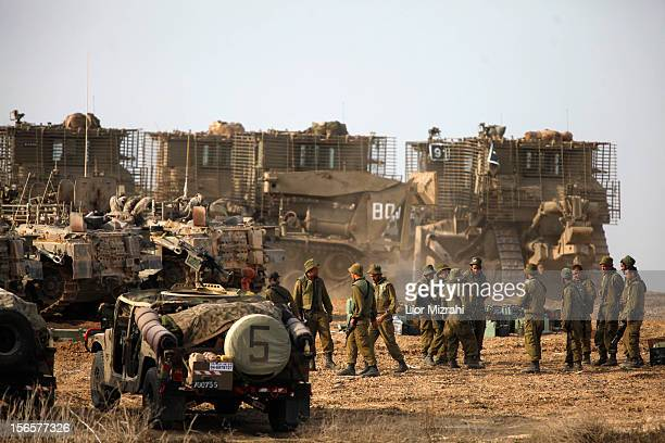 Israeli soldiers gather next to their armoured personnel carriers stationed on Israel's border with the Gaza Strip on November 17 in Israel At least...
