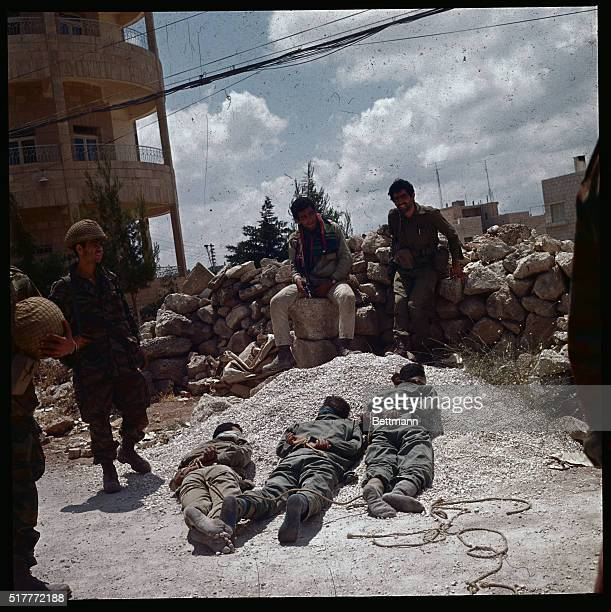 Israeli soldiers guard three Jordanian prisoners who are prone and bound on the ground, following the Israeli liberation of Jerusalem.