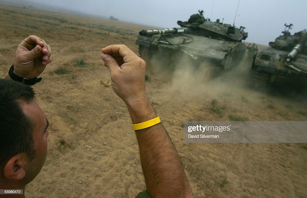 Israeli soldiers guide a Merkeva tank into place in the morning mist near the border with the Gaza Strip August 15, 2005 in the fields of Kibbutz Mefalsim in southern Israel. The Israeli army has deployed hundreds of tanks and armored vehicles and thousands of troops to defend the Jewish state's historic withdrawal from the Gaza Strip after a 38-year occupation.