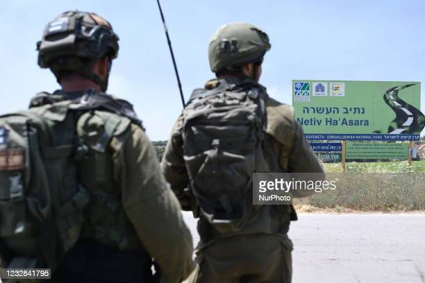 Israeli soldiers hold positions at Netiv Ha'Asara near the site where an IDF vehicle was directly hit by a rocket fired from Gaza strip, injuring 2...