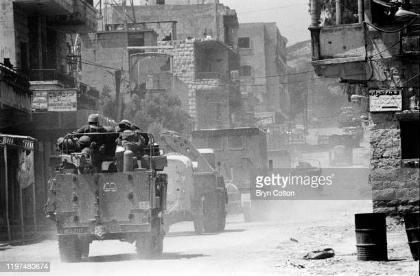 Israeli soldiers in armoured vehicles travel past houses as they pass through a village in the Bekaa Valley during the Israeli invasion of Lebanon,...