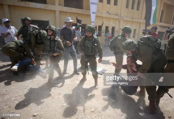 Israeli soldiers intervene in Palestinians during a protest against Israeli Prime Minister Benjamin Netanyahu's statements on an area near Jordan...
