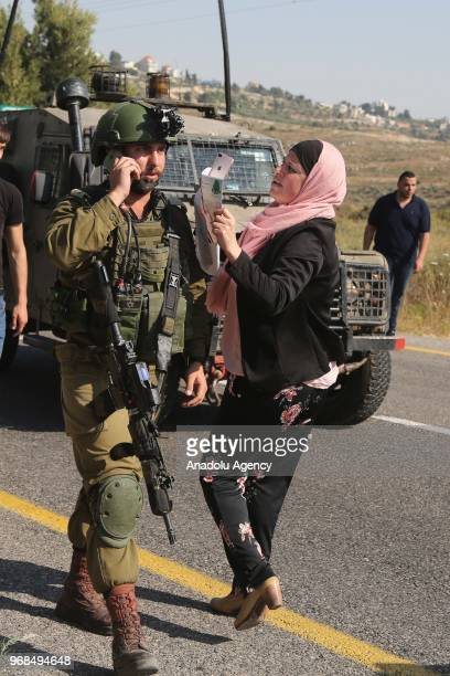 Israeli soldiers intervene Palestinians as they transport the body of Ezz alTamimi who was killed by Israeli forces at a checkpoint near Ramallah...