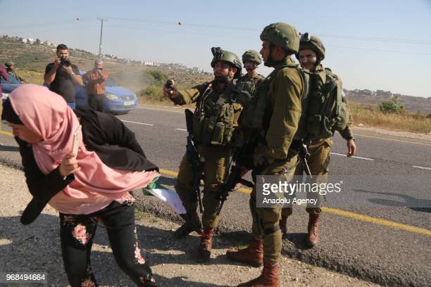Israeli soldiers intervene Palestinians with tear gas as they transport the body of Ezz alTamimi who was killed by Israeli forces at a checkpoint...