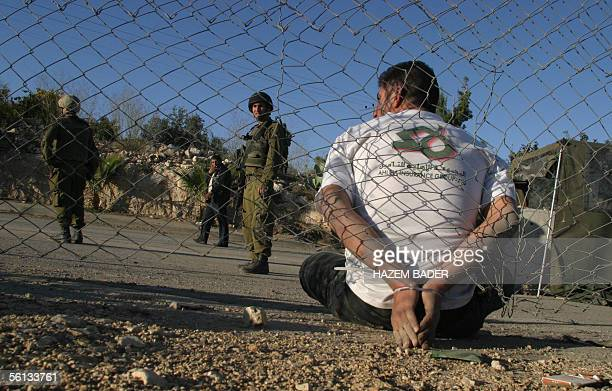 Israeli soldiers keep an eye on an arrested Palestinian youth following a stonethrowing incident during a demonstration marking the first anniversary...