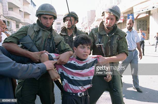 Israeli soldiers lead away a Palestinian boy in Hebron after a clash on the day of the signing of the selfrule accord