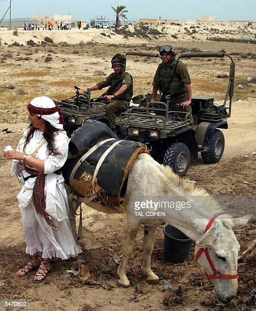 Israeli soldiers look at a woman dressed in a ceremonial dress in the Jewish settlement of Gush Katif in the southern Gaza Strip 27 April 2004...