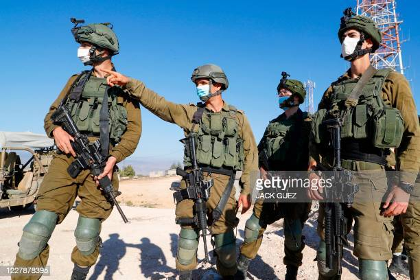 Israeli soldiers monitor the country's border with Lebanon near the northern town of Metula, on July 14, 2020. - On either side of the...