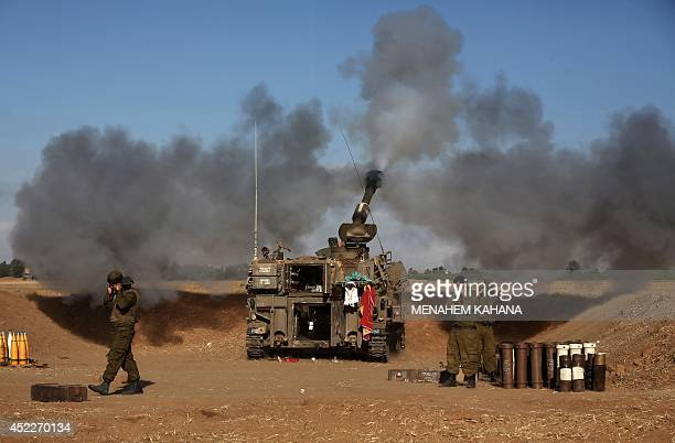 Israeli soldiers of the 155mm artillery canons unit fire towards the Gaza Strip from their position near Israel's border with the coastal Palestinian...