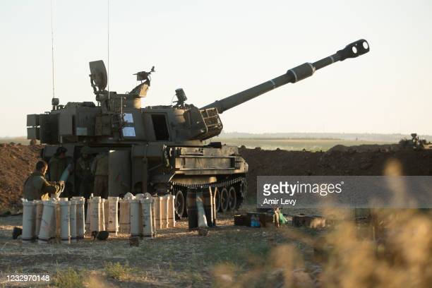 Israeli soldiers operate an artillery unit as it fires near the border between Israel and the Gaza Strip on May 18, 2021 in Sderot, Israel. In a...