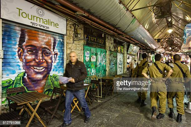 Israeli soldiers pass in front of a graffiti depicting an unrecognized person which was painted over a closed shutter at the Mahane Yehuda Market...