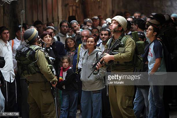 Israeli soldiers patrol a street near Palestinian homes as Israelis make a promenade along a street, in the West Bank town of Hebron, during Sukkot...