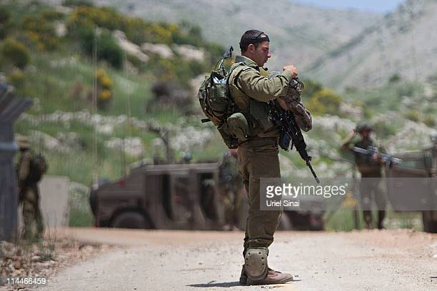 Israeli soldiers patrol along the border fence between the Israeliannexed Golan Heights and Syria on May 20 2011 near the Druze village of Majdal...