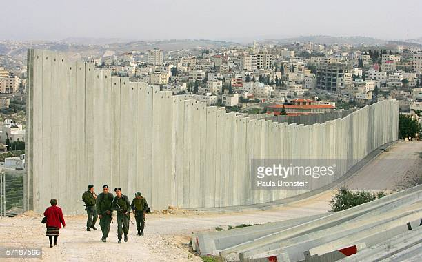 Israeli soldiers patrol along the concrete separation barrier bordering Abu Dis, West Bank March 26, 2006 in East Jerusalem, Israel. The...