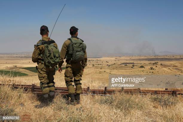Israeli soldiers patrol near the border with Syria after projectiles fired from the wartorn country hit the Israeli occupied Golan Heights on June 24...