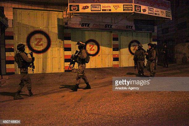 Israeli soldiers patrol to search three young Jewish settlers at the Hebron streets West Bank on June 17 2014 The fourday closure had come as part of...