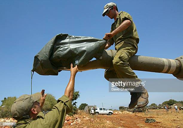 Israeli soldiers place a protective cover over the cannon of a 155mm mobile artillery piece as a battery of Israel's heavy guns deploys August 11...