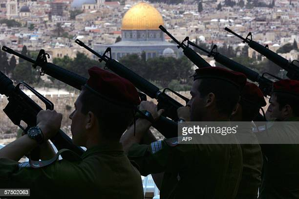 Israeli soldiers practice the honor salute at the military cemetery on the Mount of Olive overlooking the Dome of the Rock mosque in Jerusalem 01 May...