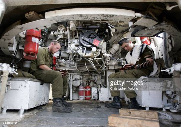 Israeli soldiers pray inside the loading compartment of their 155mm artillery gun as the barrage against Hezbollah targets in South Lebanon continues...