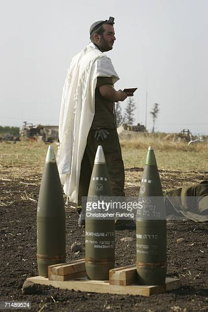 Israeli soldiers pray next to their 155mm artillery guns during the barrage against Hezbollah targets in South Lebanon July 20 2006 from a forward...