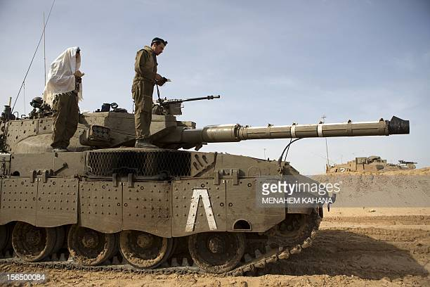 Israeli soldiers pray on their tank stationed at the IsraeliGaza Strip border on November 16 2012 Israeli officials said the Jewish state was...