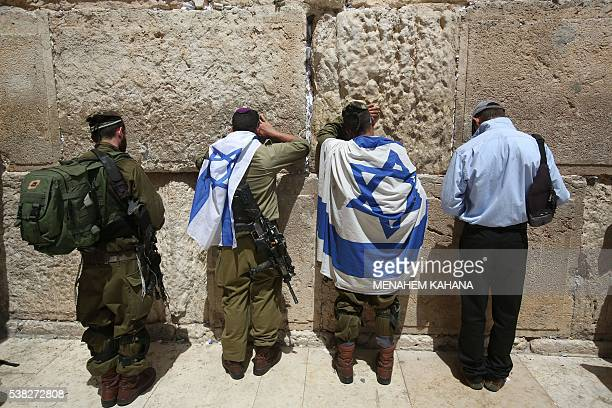 Israeli soldiers pray with their national flags at the Western Wall on June 5 2016 in Jerusalem's old city as they celebrate Jerusalem Day that marks...