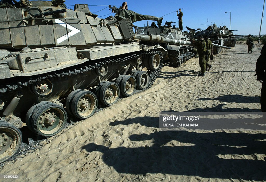 Israeli soldiers prepare their tanks just before they moves into the outskirts of the southern Gaza Strip town of Rafah 20 May 2004, on the third day of the massive Israeli army operation in the area. A total of 41 Palestinians have been killed since the Israeli army launched the Rafah raid early 18 May, dubbed 'Operation Rainbow' and aimed at stopping arms smuggling from Egypt through cross-border tunnels.