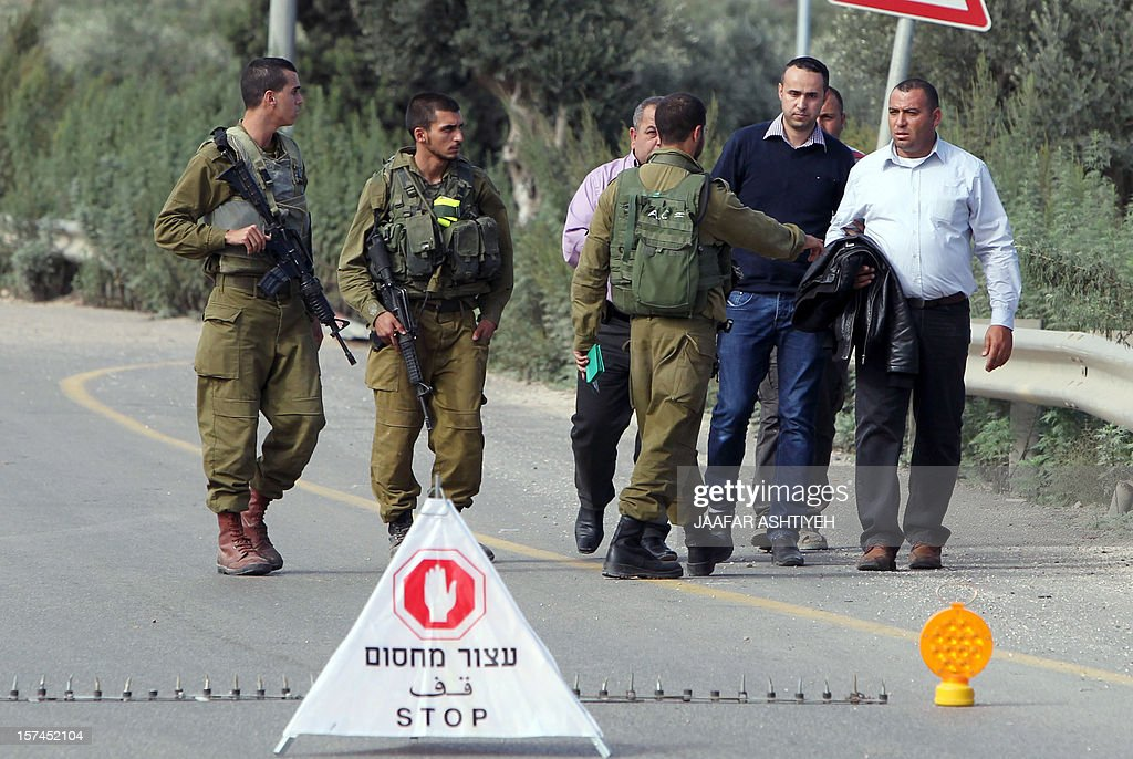 Israeli soldiers prevent a man (C) from going to see the body of his brother, Hatem Shadid, who was shot dead earlier by Israeli forces from the Shin Bet internal security agency after he rammed their car and attacked them with an axe on December 3, 2012 in the West Bank area of Deir Sharaf.