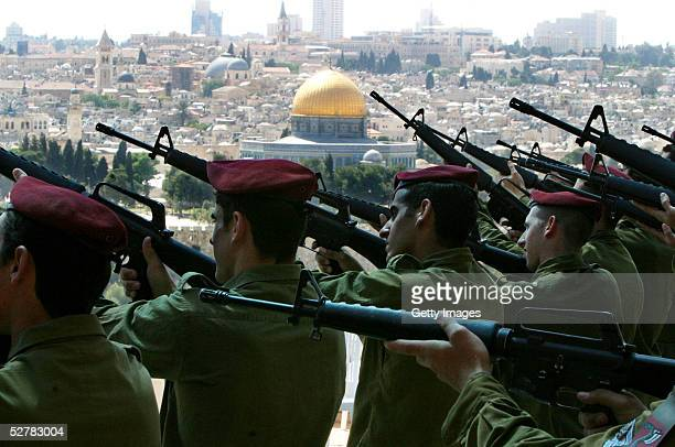 Israeli soldiers raise their weapons to fire an honor volley while rehearsing ahead of Memorial Day to commemorate Israeli soldiers killed in wars...