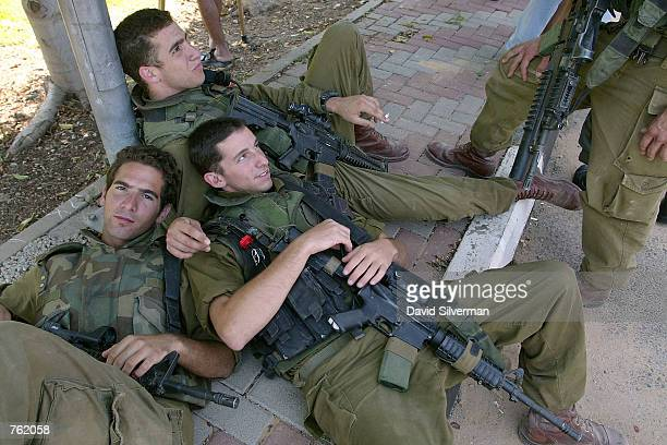 Israeli soldiers relax following their searches of the area shortly after a Palestinian suicide bomber blew himself up alongside a police patrol jeep...