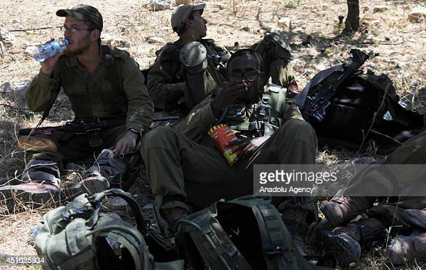 Israeli soldiers rest after patrolling the area during a search for three missing Israeli teenagers in Hebron West Bank on 21 June 2014