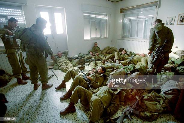 Israeli soldiers rest after they took position in a Palestinian house that was not inhabited November 22 2002 in Beit Jala near the West Bank city of...